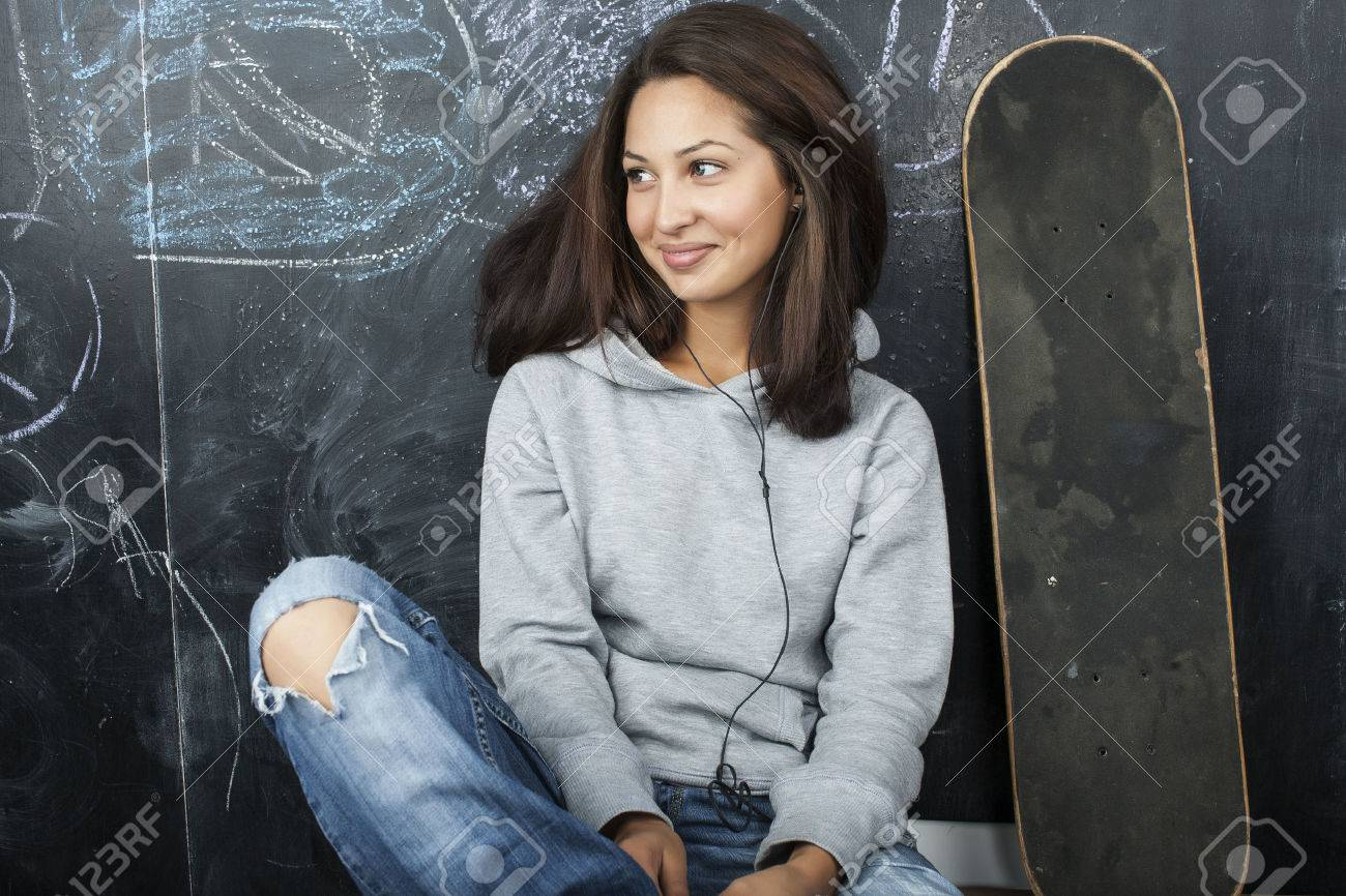 young cute teenage girl in classroom at blackboard seating on table smiling, modern hipster concept - 52083597