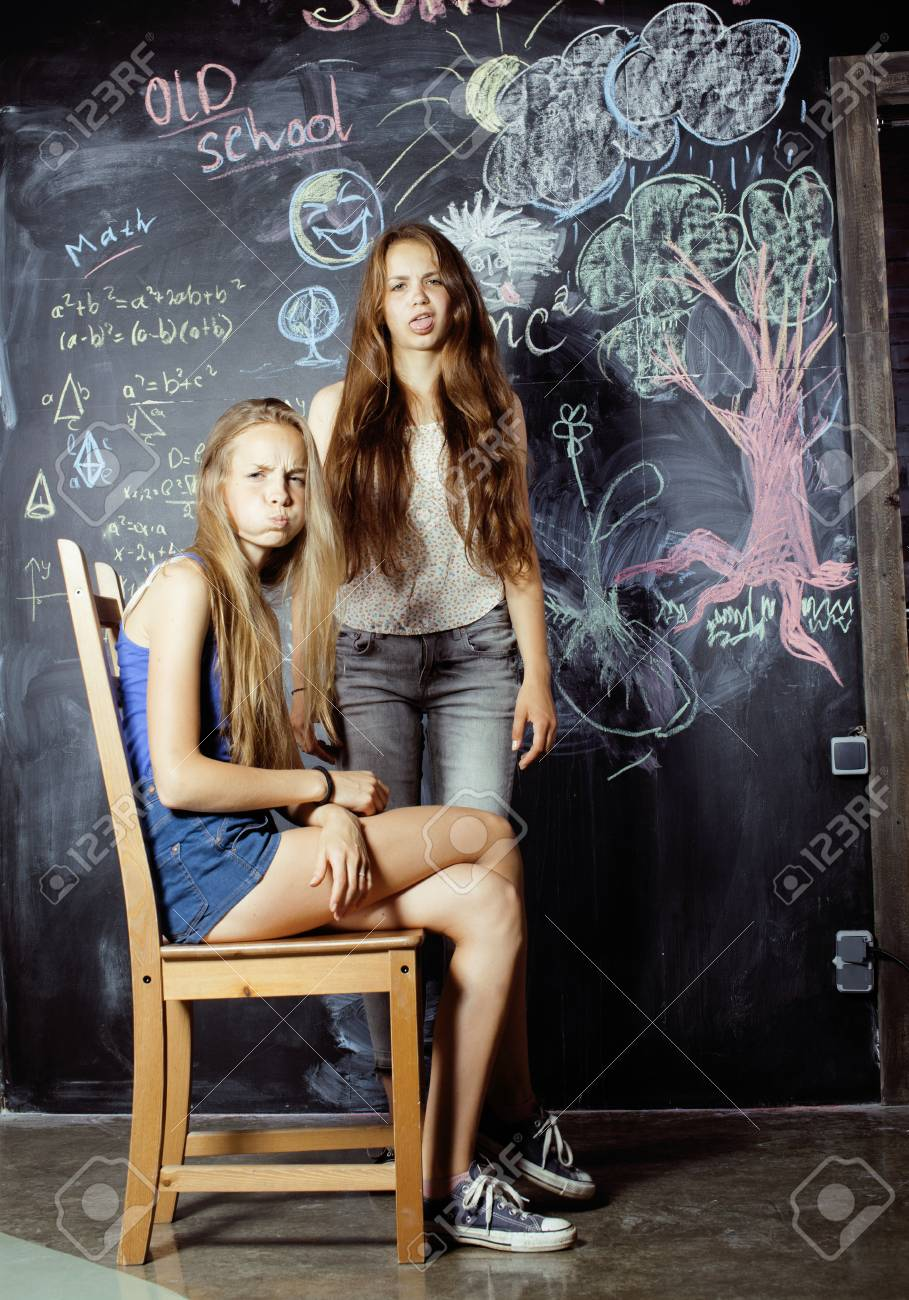 back to school after summer vacations, two teen real girls in classroom  with blackboard painted