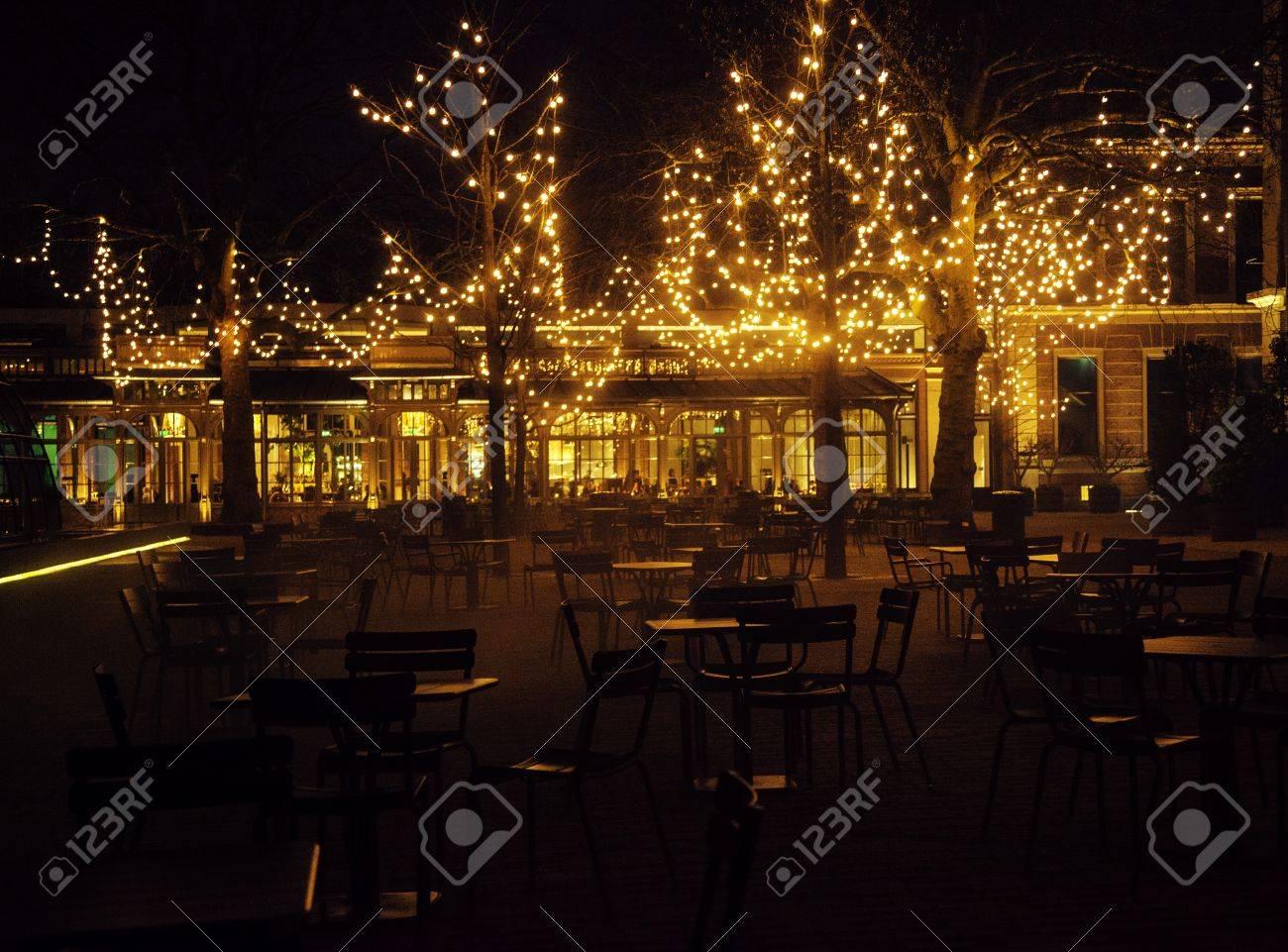 24722378753d Foto de archivo - Noche restaurante vacío, gran cantidad de mesas y sillas  con nadie, luces de colores mágicos en los árboles como celebración
