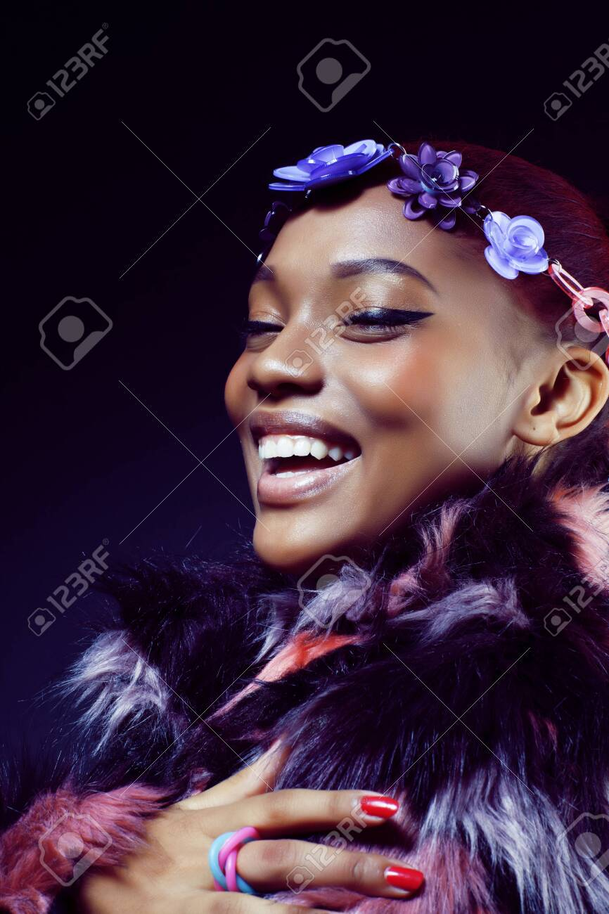 young pretty african american woman in spotted fur coat and flow - 130186466