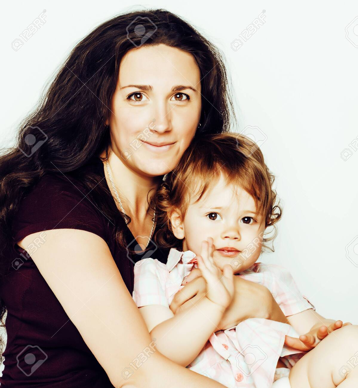 young modern smiling brunette mother with little cute daughter on white background, happy girls family inside isolated adorable - 120781615