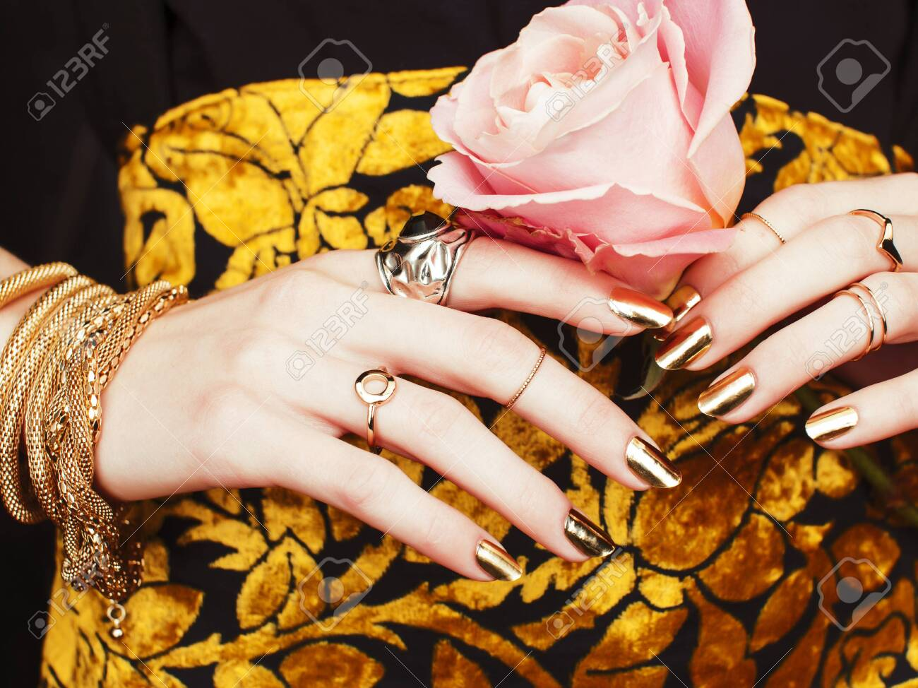 woman hands with golden manicure lot of jewelry on fancy dress close up beauty concept - 120784496