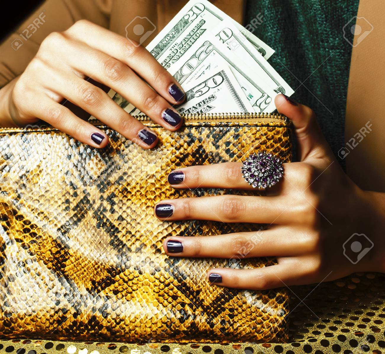 pretty fingers of african american woman holding money close up with purse, luxury jewellery on python clutch, cash for gifts - 121254509