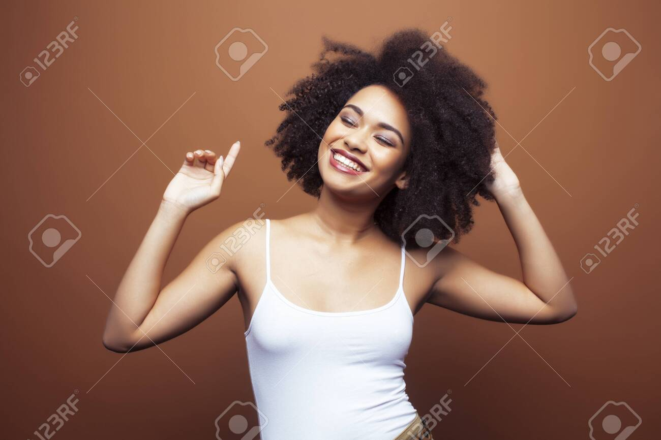 pretty young african american woman with curly hair posing cheerful gesturing on brown background, lifestyle people concept - 134796126