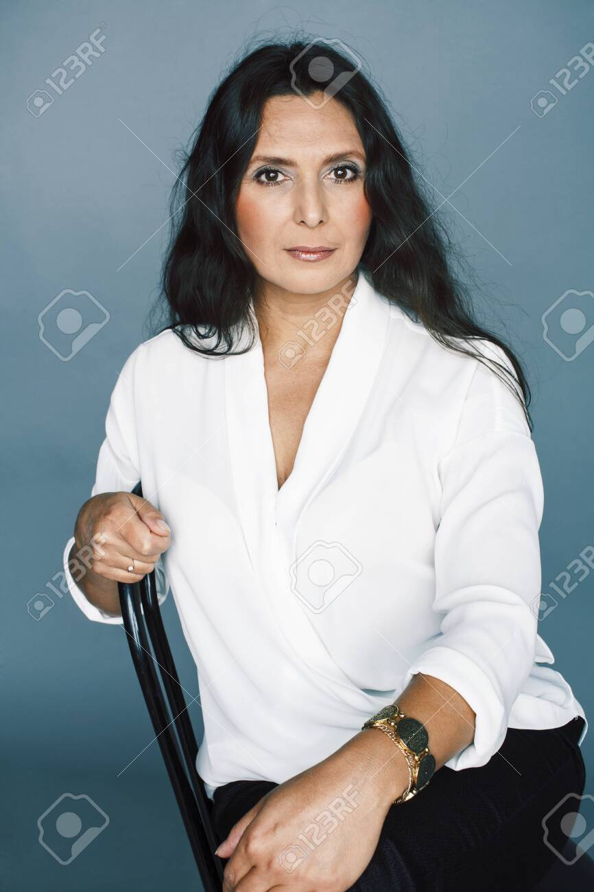 pretty brunette confident mature woman sitting on chair in studio, lifestyle people concept - 142605600
