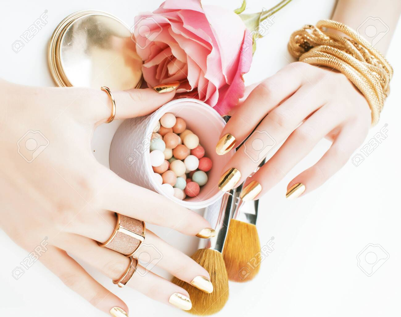woman hands with golden manicure and many rings holding brushes, makeup artist stuff stylish, pure close up pink flower rose among cosmetic for makeup - 143450788