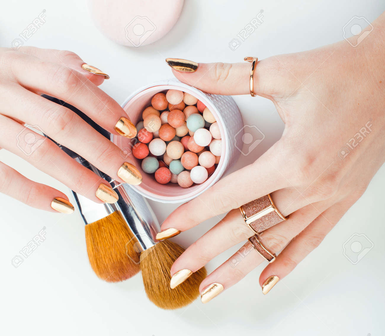 woman hands with golden manicure and many rings holding brushes, makeup artist stuff stylish, pure closeup pink flower rose among cosmetic for makeup - 151456005