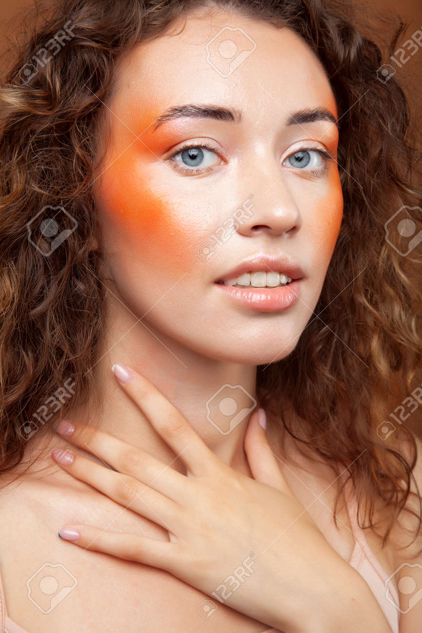 young pretty girl with curly hair posing cheerful on brown background, lifestyle people concept - 153457812