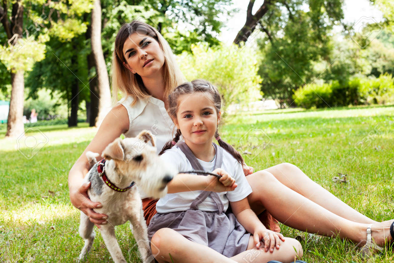 young pretty caucasian mother walking with little cute daughter and dog fox terrier, lifestyle people concept - 153460454