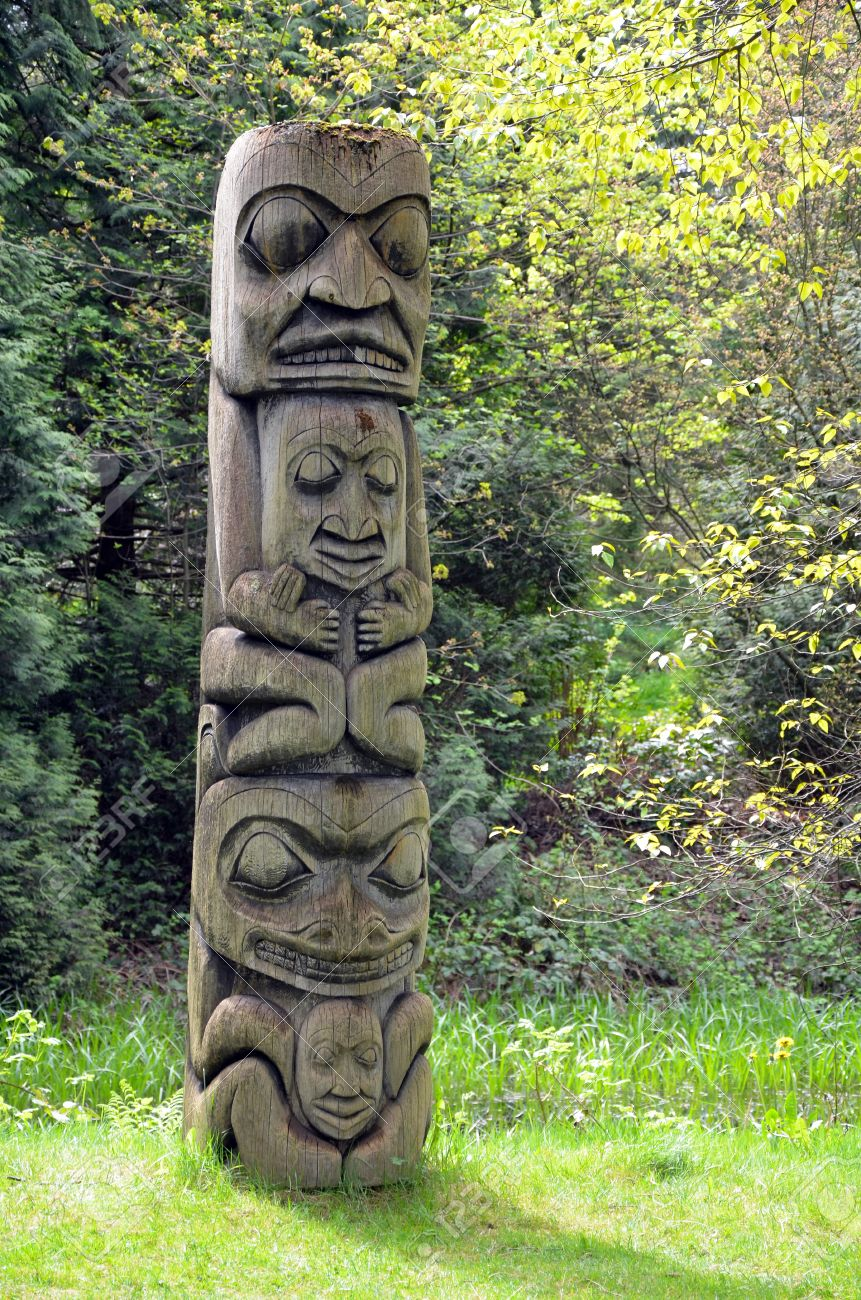 weathered totem pole in pacific northwest forest stock photo