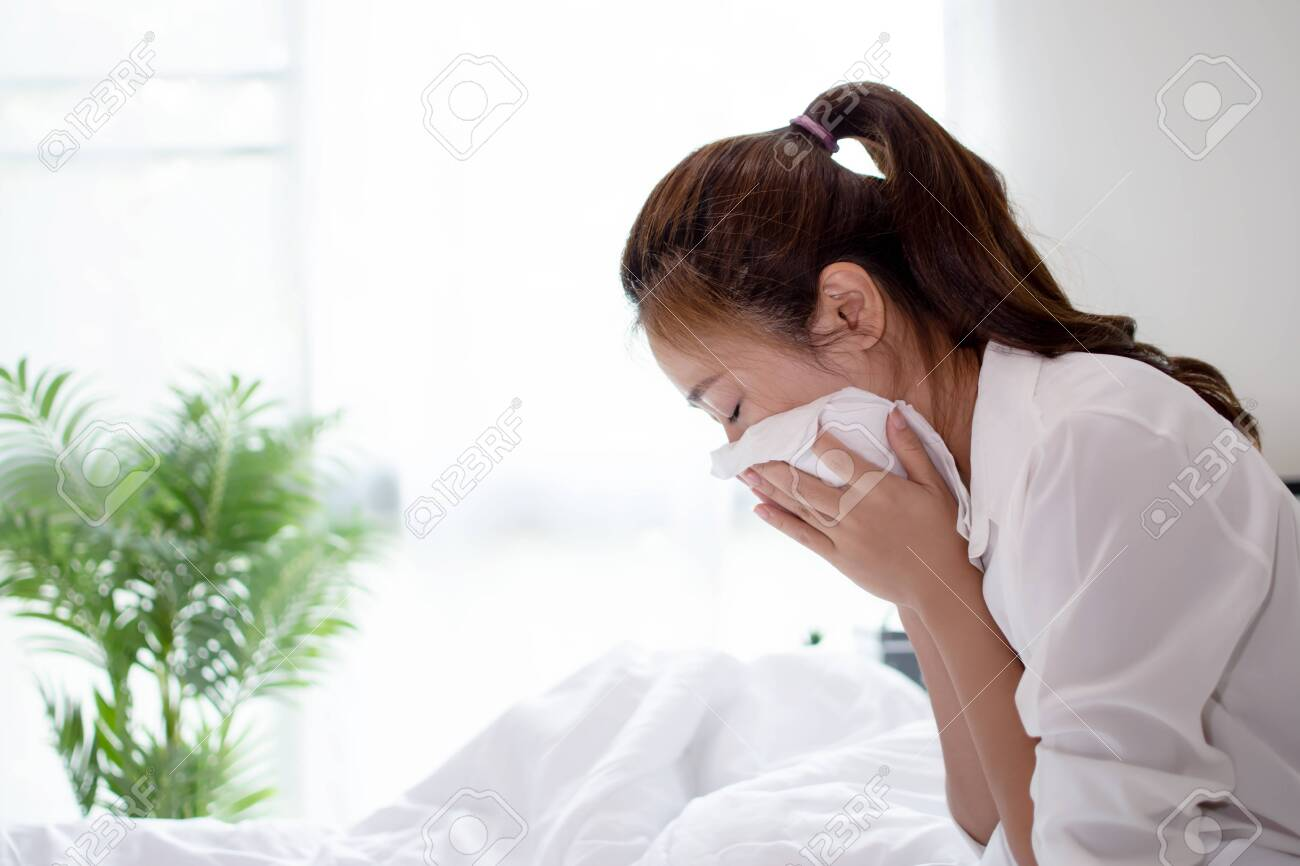 Business woman is sick and sneezing hard on the bed. - 150509401