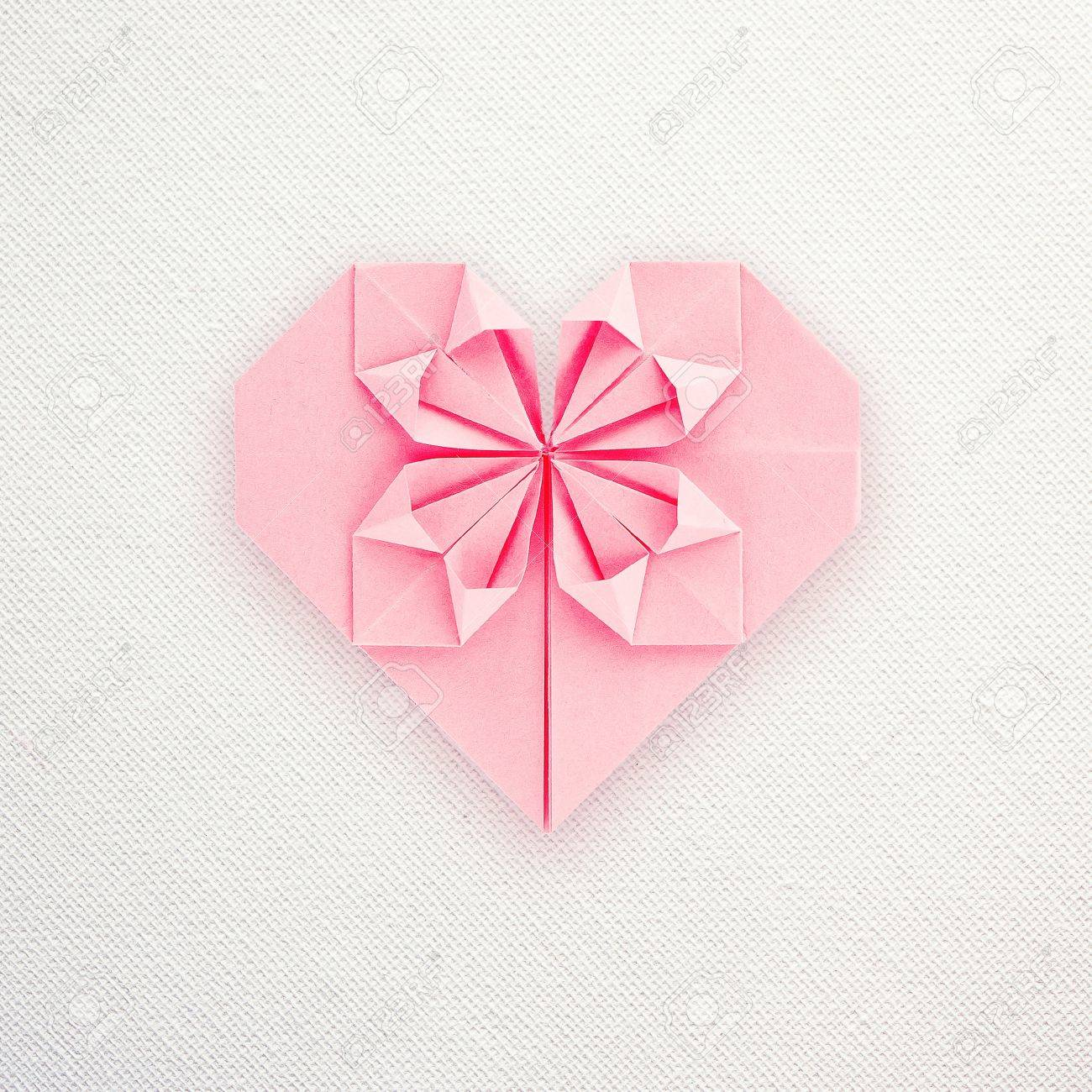 A pink paper origami heart on white canvas back Stock Photo - 17775858