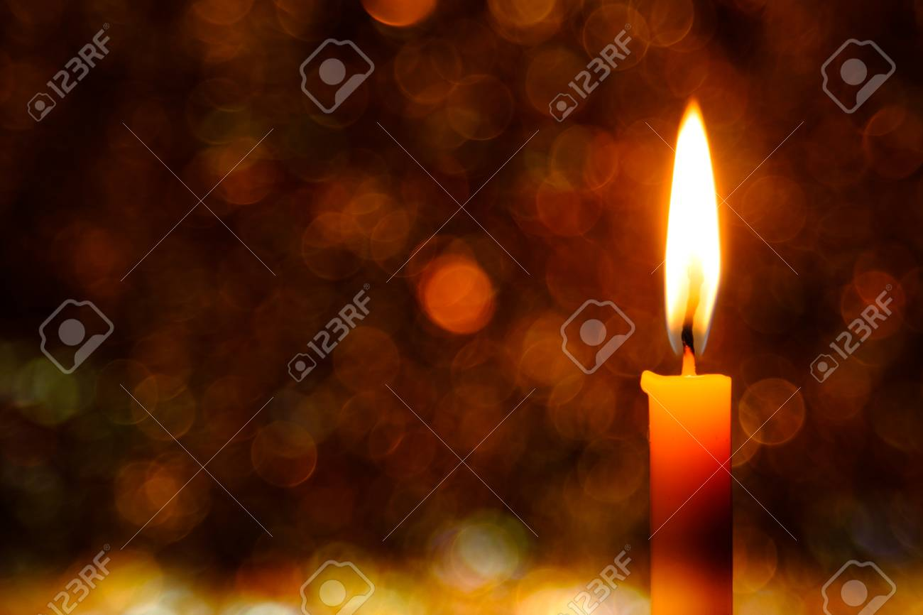 candle flame light at night with abstract circular bokeh background christmas lights stock photo