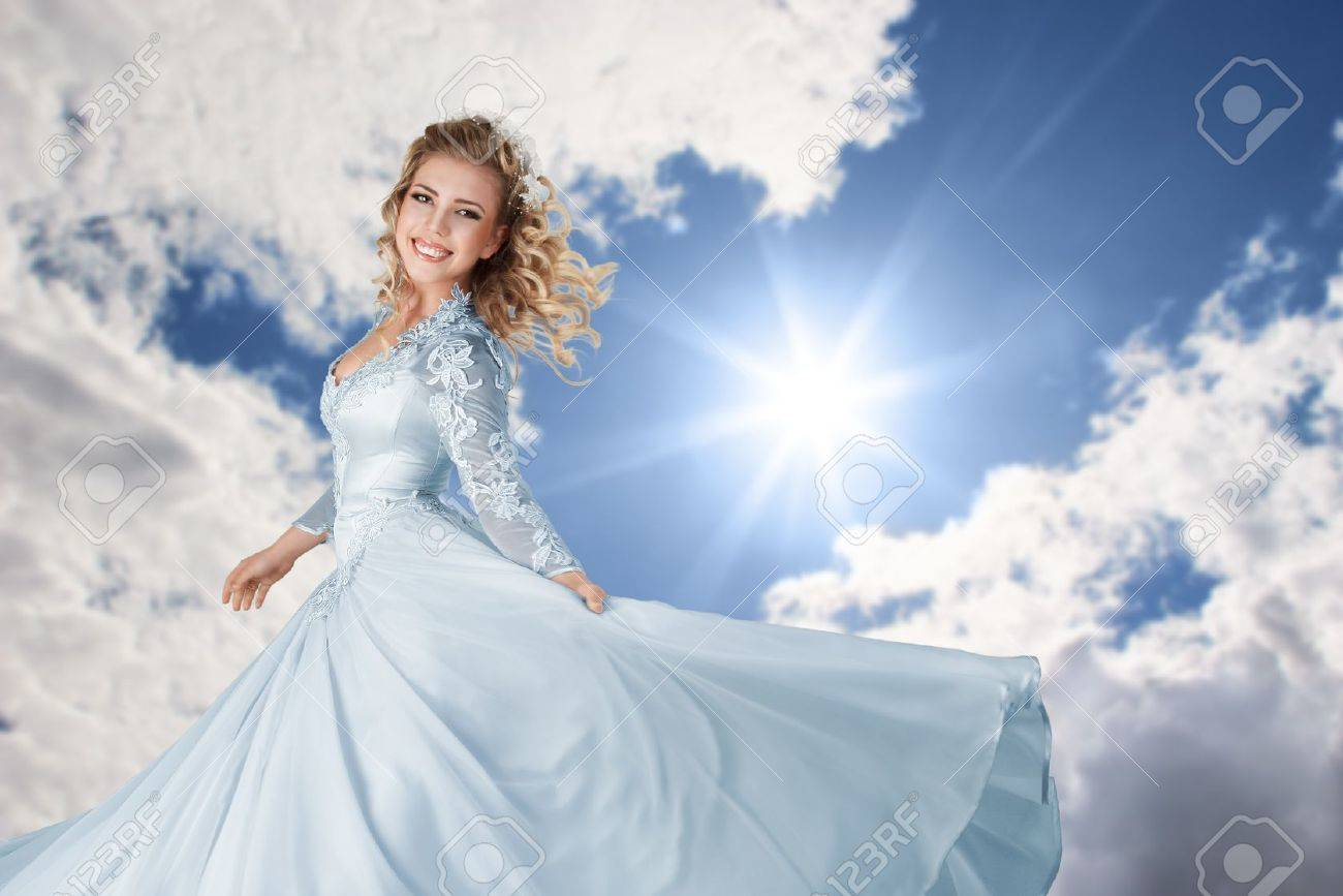 Happy young bride in long beautiful dress against blue bright sunny sky Stock Photo - 15408249