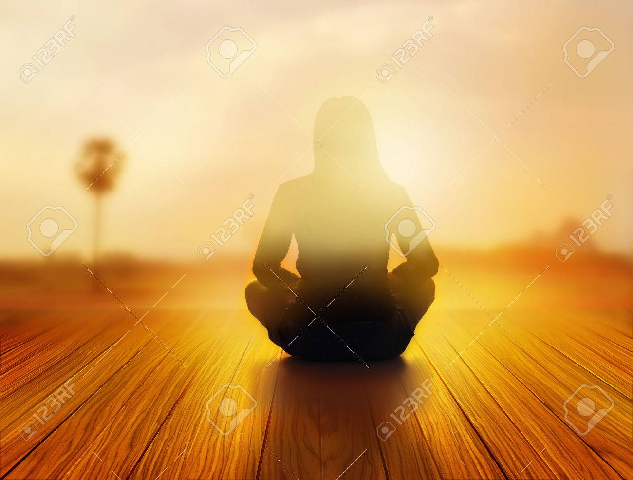 Woman was meditating in sunrise and rays of light on landscape stock photo woman was meditating in sunrise and rays of light on landscape soft and blur concept aloadofball Gallery