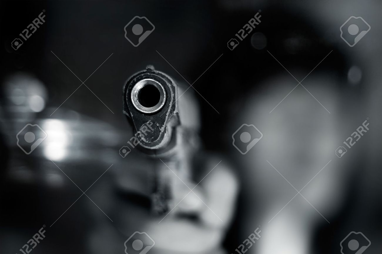 Black and white, woman pointing a old gun to front with one Hand on dark background - 44278325