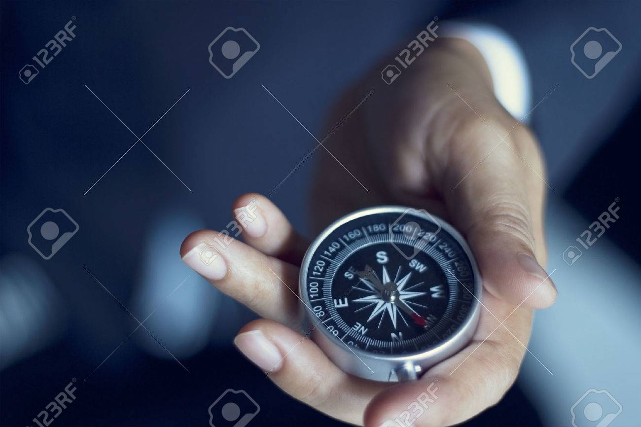 Businessman with a compass holding in hand, color tone film look Stock Photo - 49683346