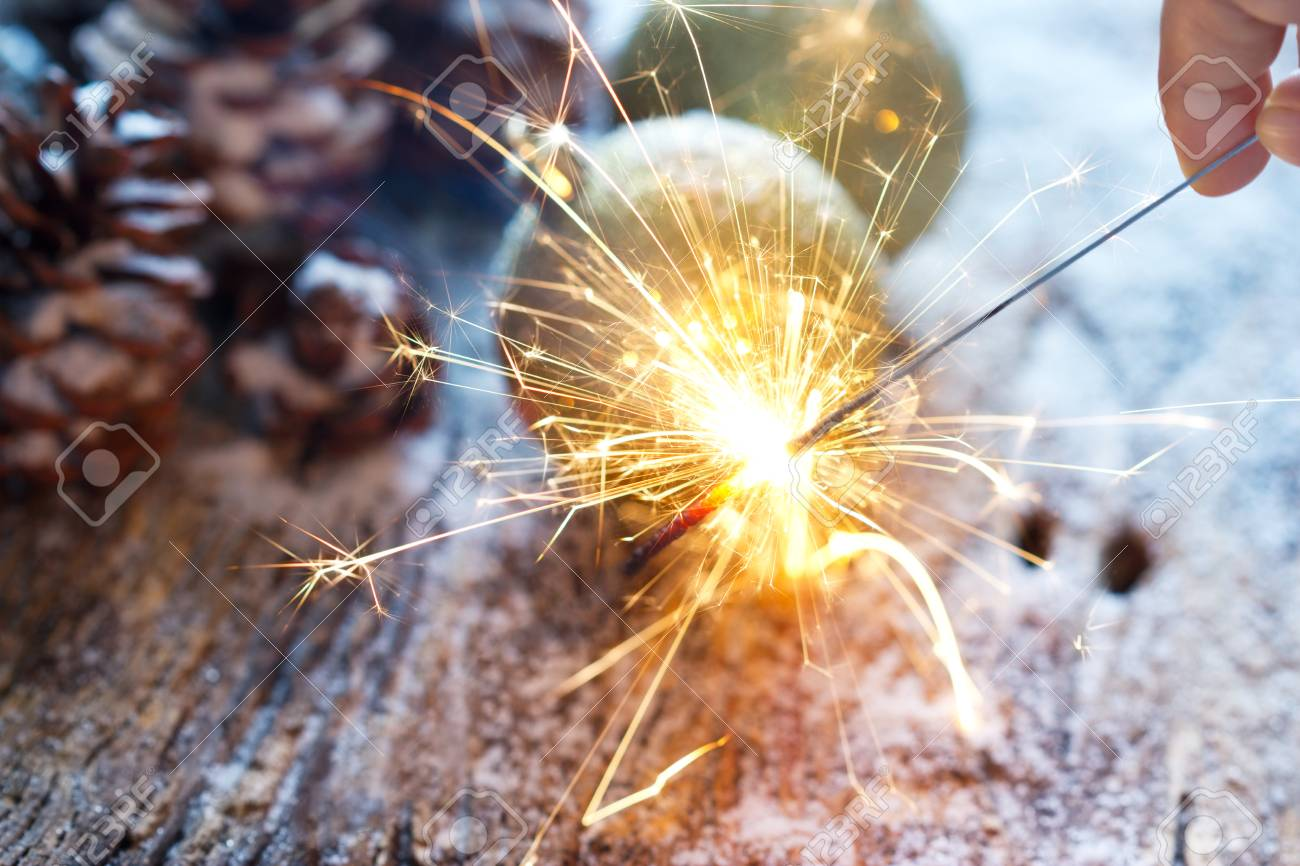 Stock Photo  Firework Or Electric Sparklers In Hand On Christmas Ornament  Pine Cones Background