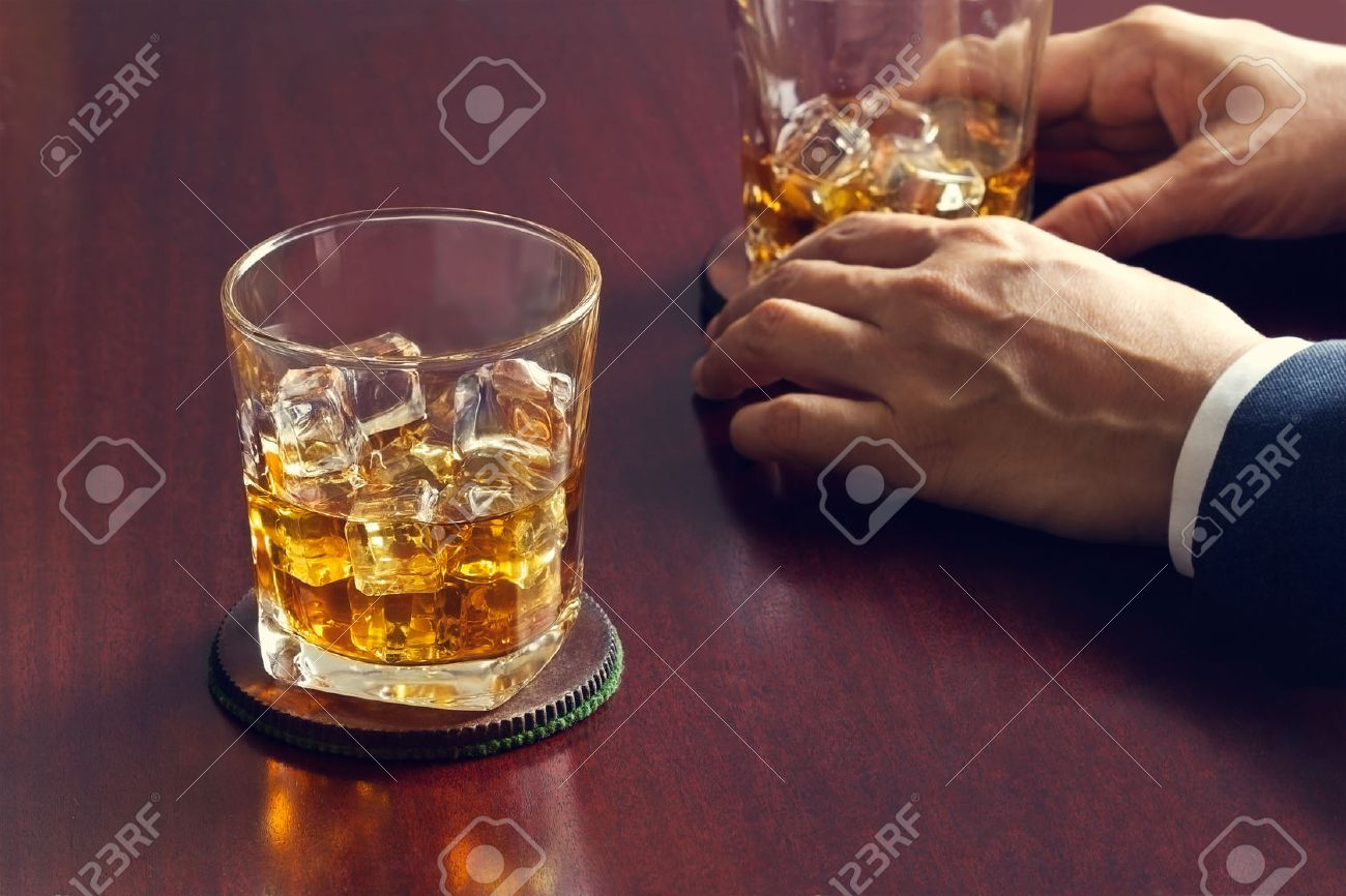 Whiskey on wooden table and businessman with whiskey in hand Standard-Bild - 52579784