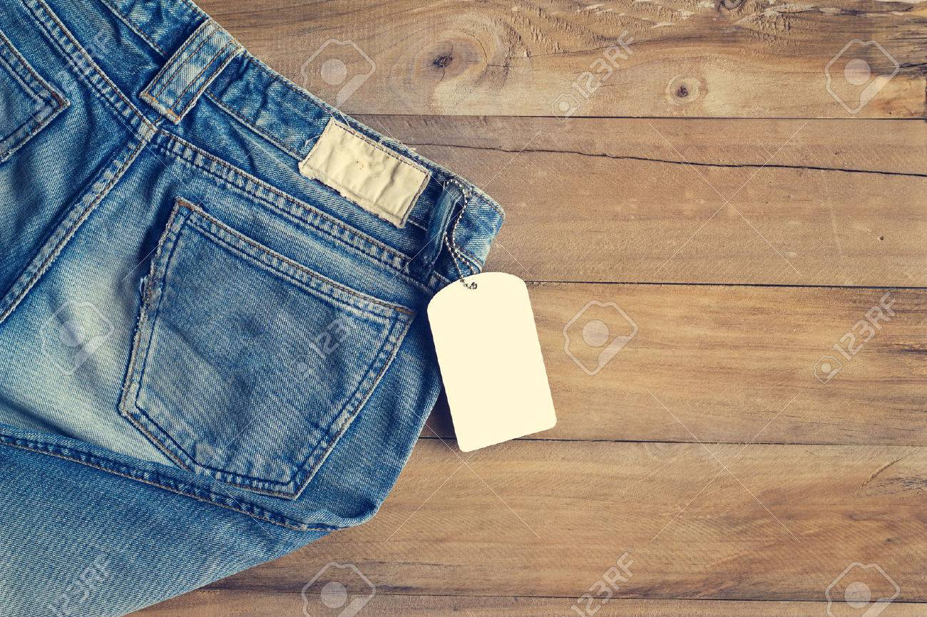 Blue jeans with white blank tag on wooden background Standard-Bild - 52579793