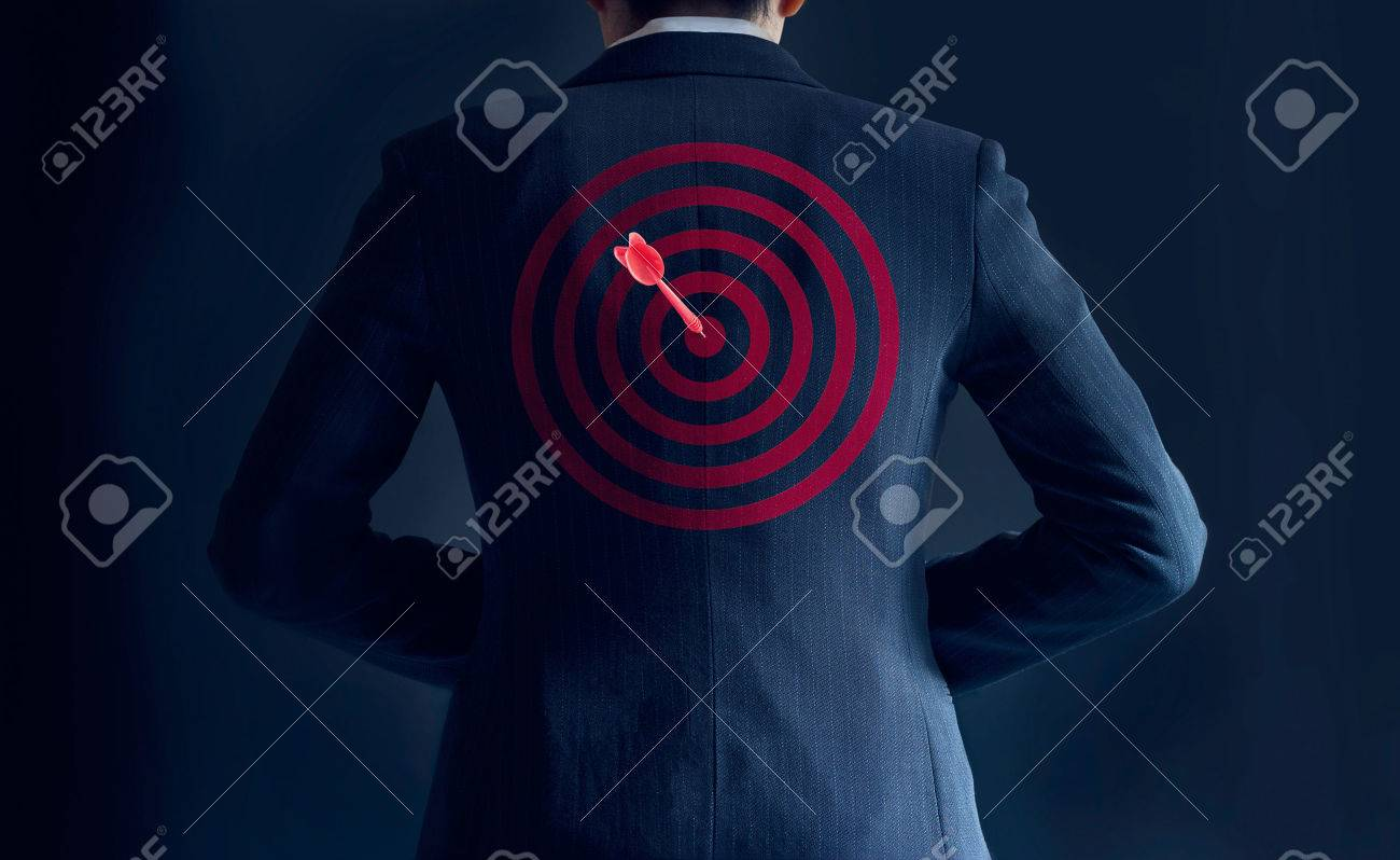 businessman get success with red arrow on target at the back of his suit on dark background, business concept Standard-Bild - 54938190