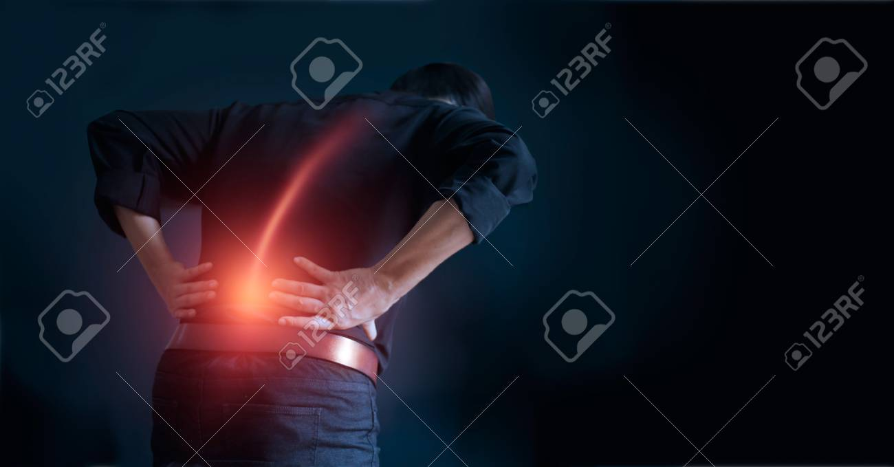 Man suffering from back pain cause of office syndrome, his hands touching on lower back. Medical and heathcare concept - 106896069
