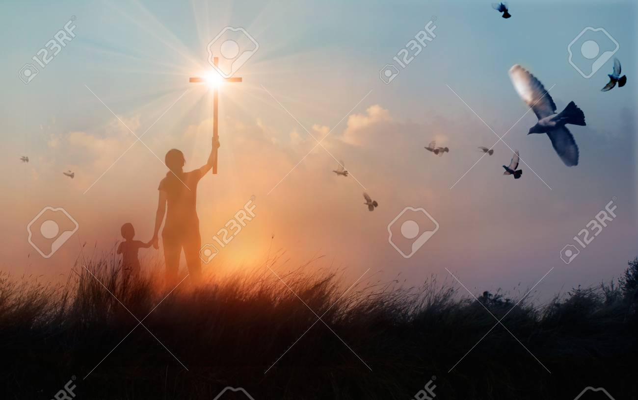 Silhouette of mother and son christian prayers raising cross while praying to the Jesus on sunset background, worship concept - 106896440