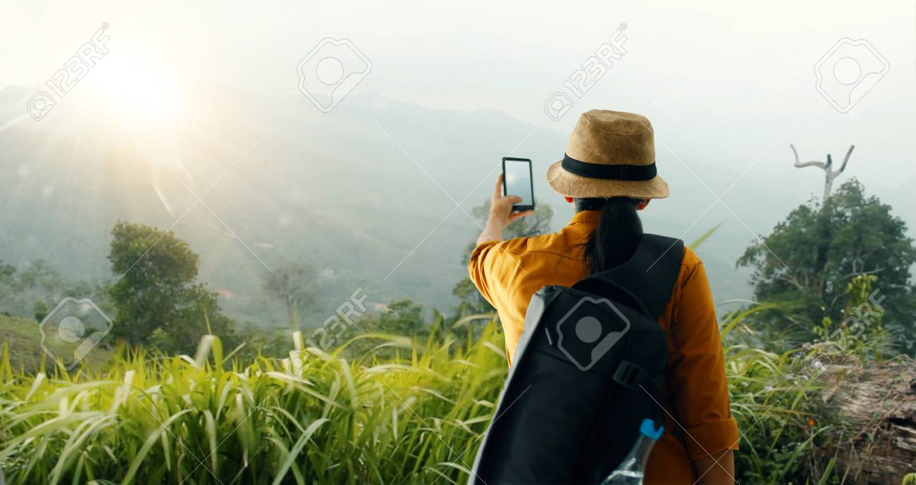 backpack using smartphone taking picture beautiful landscape on mountain peak while exploring, trekking in tropical rain forest of Asia - 109471979