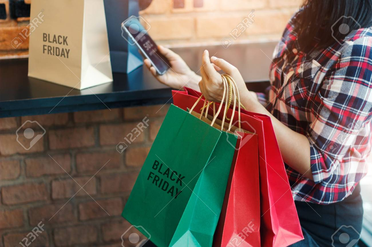 Black Friday, Woman using smartphone and holding shopping bag while sitting in the mall background - 109472561