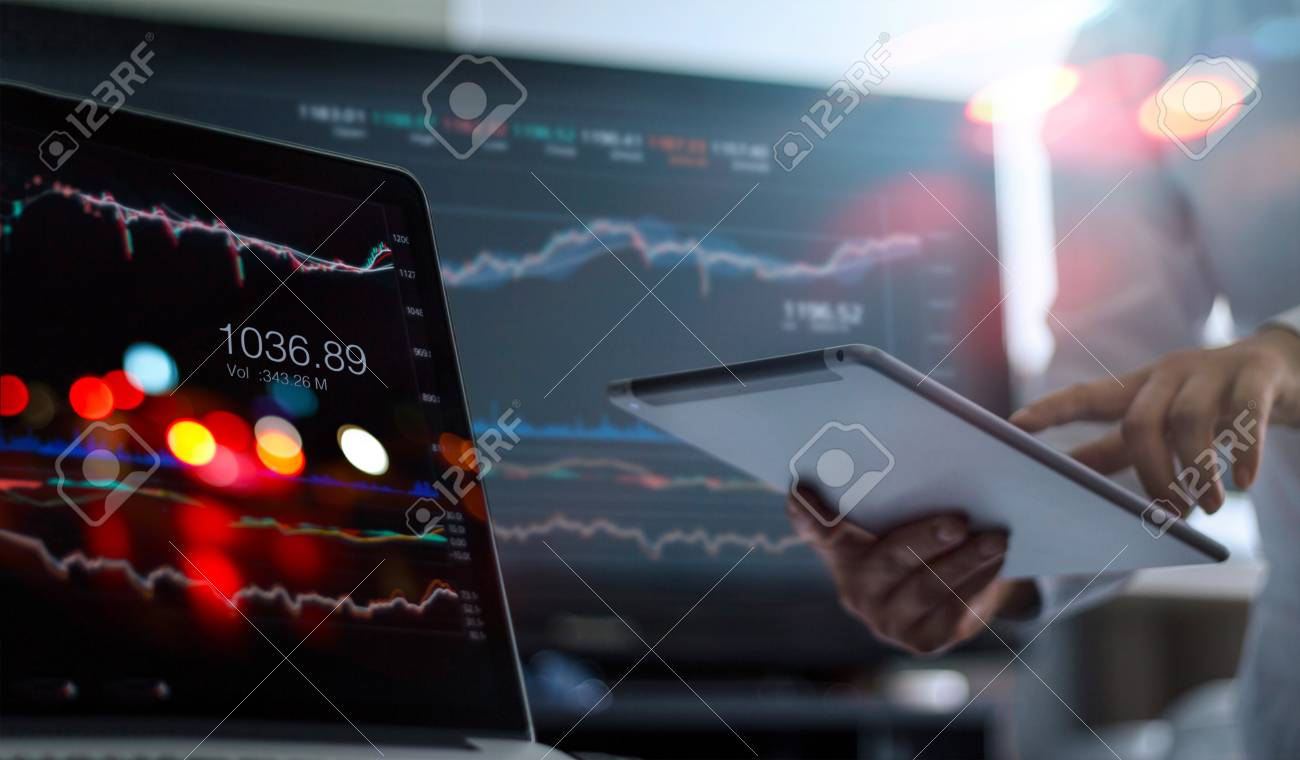 Businessman using tablet and laptop for analyzing data stock market in monitoring room background, forex trading graph, stock exchange trading online, financial investment concept. All on laptop screen are design up. - 119057677