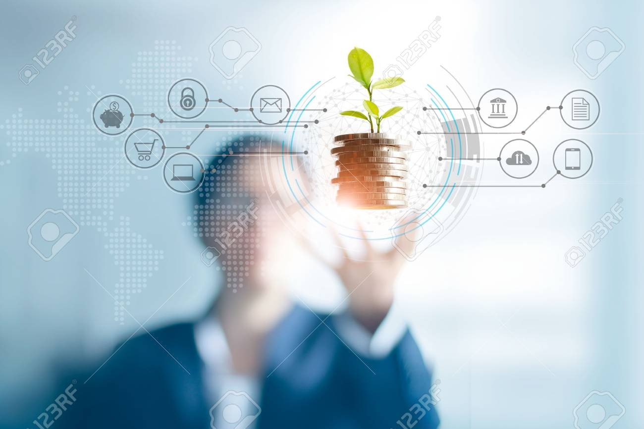 Businessman holding a tree sprout growing on coins, abstract growth investing. Finance and icon customer, banking network connection on interface, digital marketing, investment growth and business technology concept - 126271250