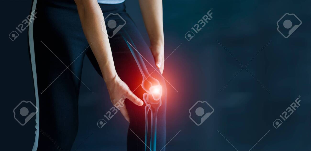 Sport woman suffering from pain in knee. Tendon problems and Joint inflammation on dark background. Healthcare and medical. - 134137549