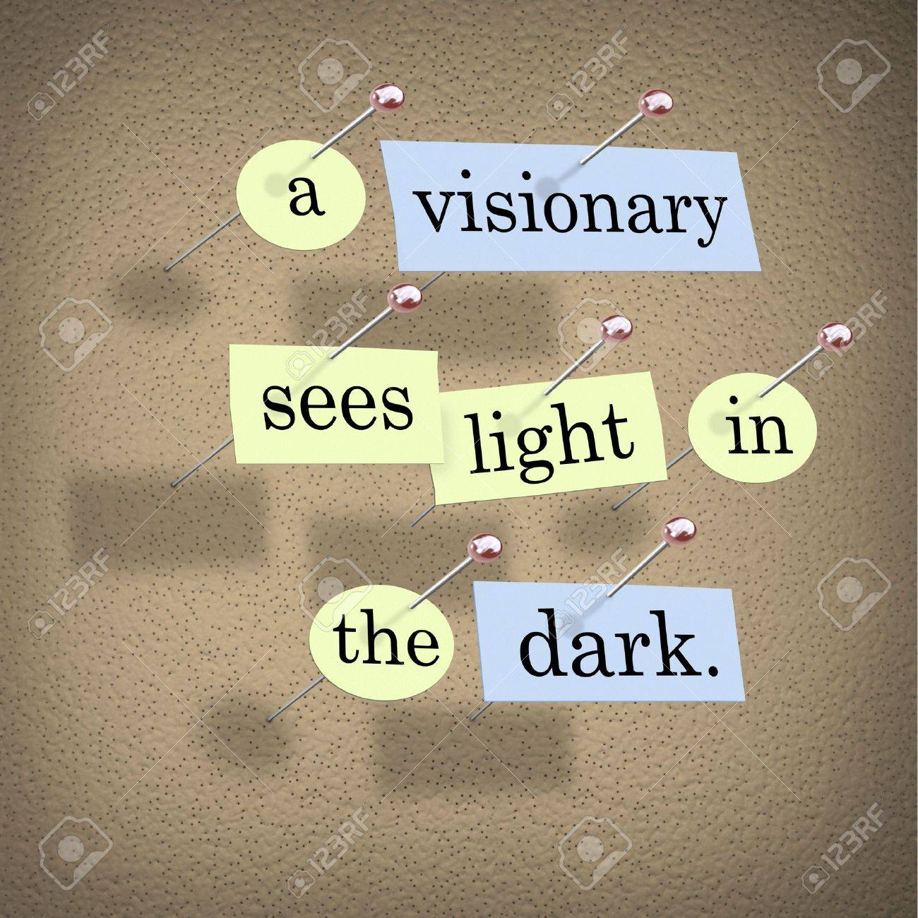 Pieces of paper each containing a word pinned to a cork board reading A Visionary Sees Light in the Dark. Stock Photo - 5861208