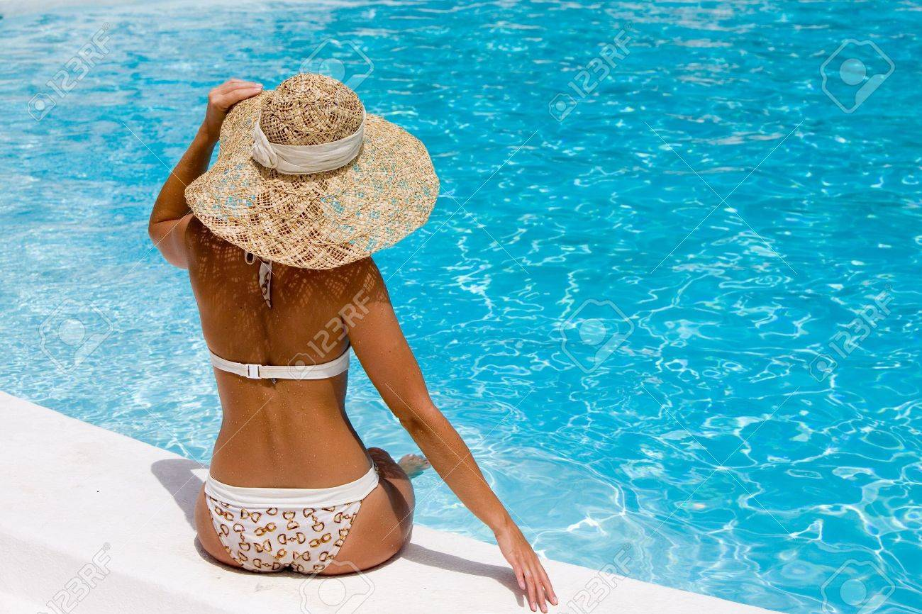 Woman in hat relaxing beside the pool - 5405000