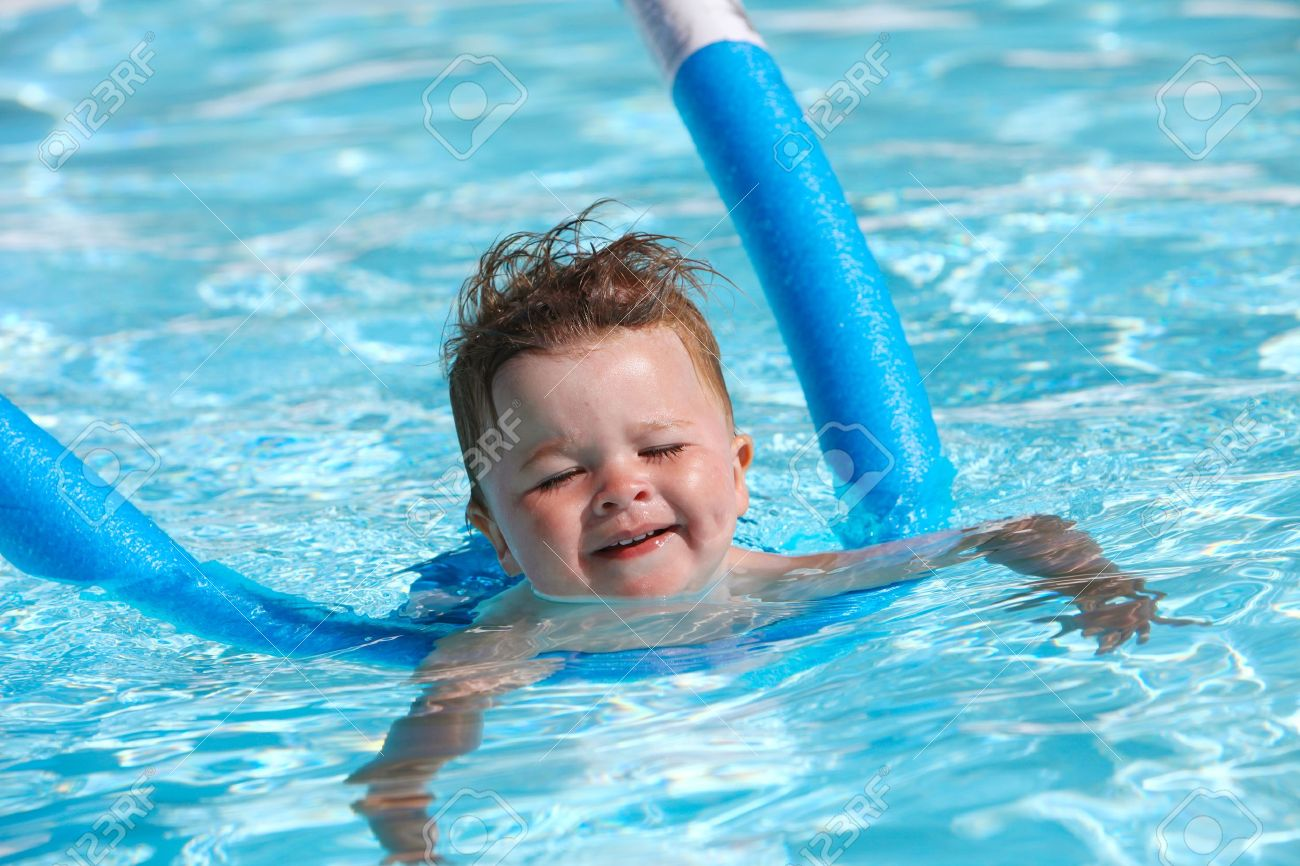 Happy little boy learning to swim with pool noodle - 15951398