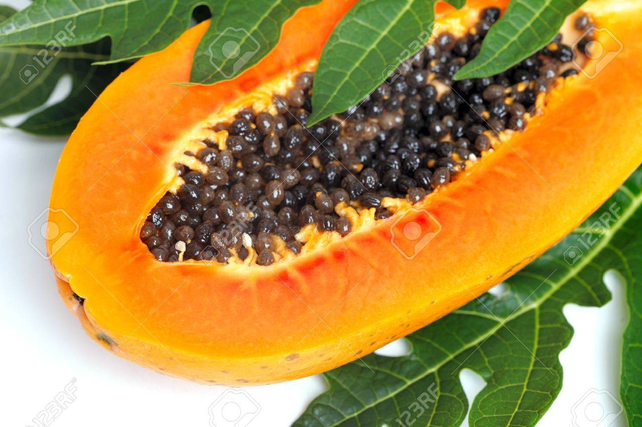 Ripe papaya with seeds and green leaf isolated on a white background - 19121592