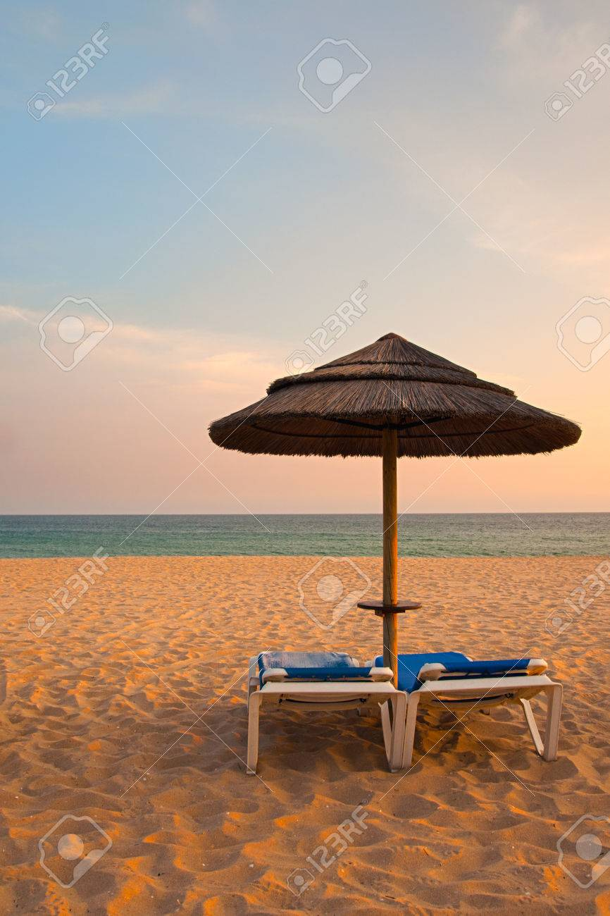 Empty deck loungers in the beach at sunset. Paradise in Algarve, Portugal Stock Photo - 23387850