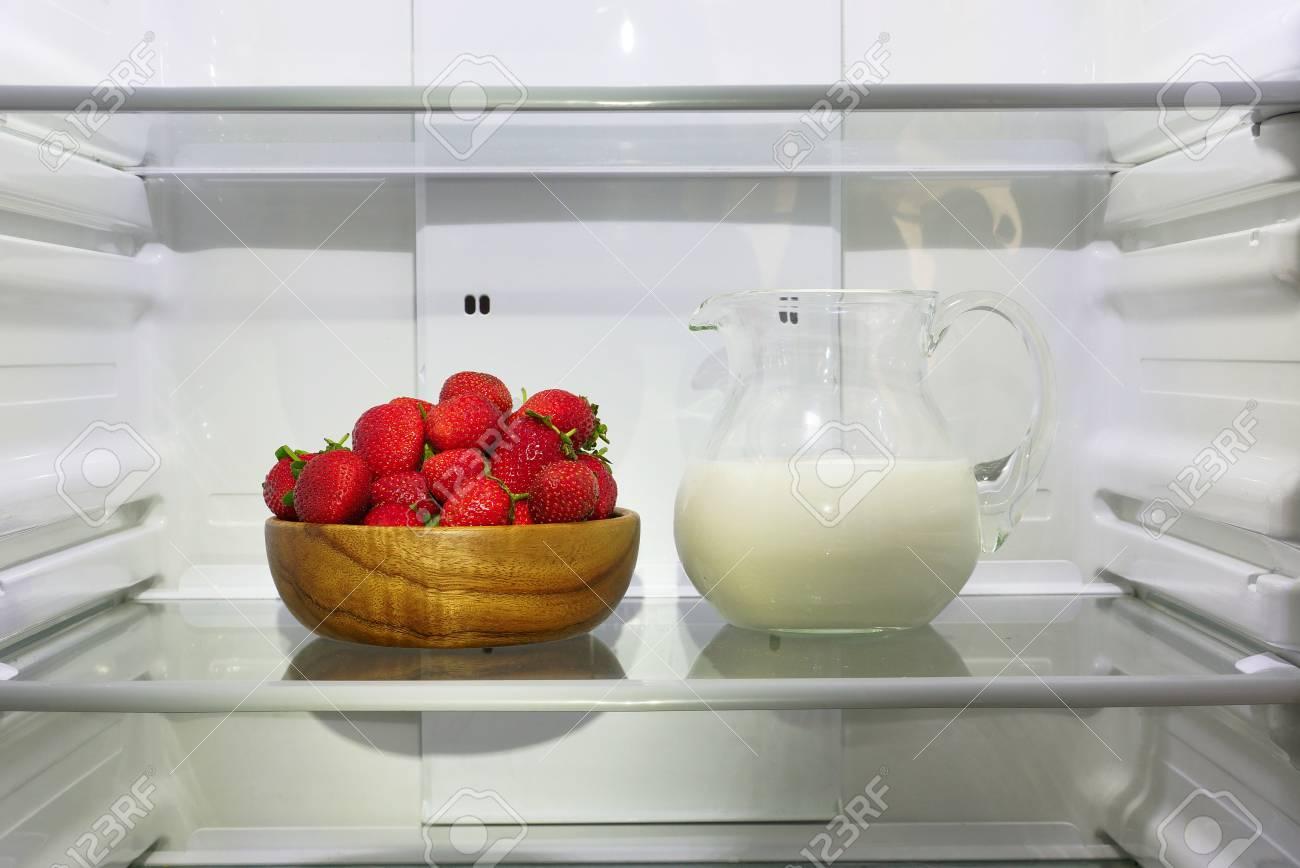 Kühlschrank Krug : Erdbeeren in einer holzschale und einem krug milch auf einem regal