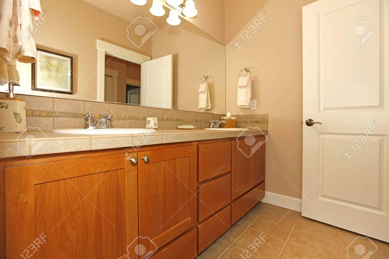 cuarto de bao en color beige con muebles bonitos y la puerta abierta foto de archivo