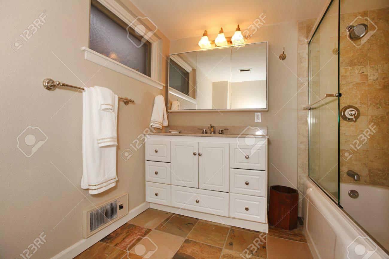 Belle salle de bains avec douche et armoires blanches. banque d ...