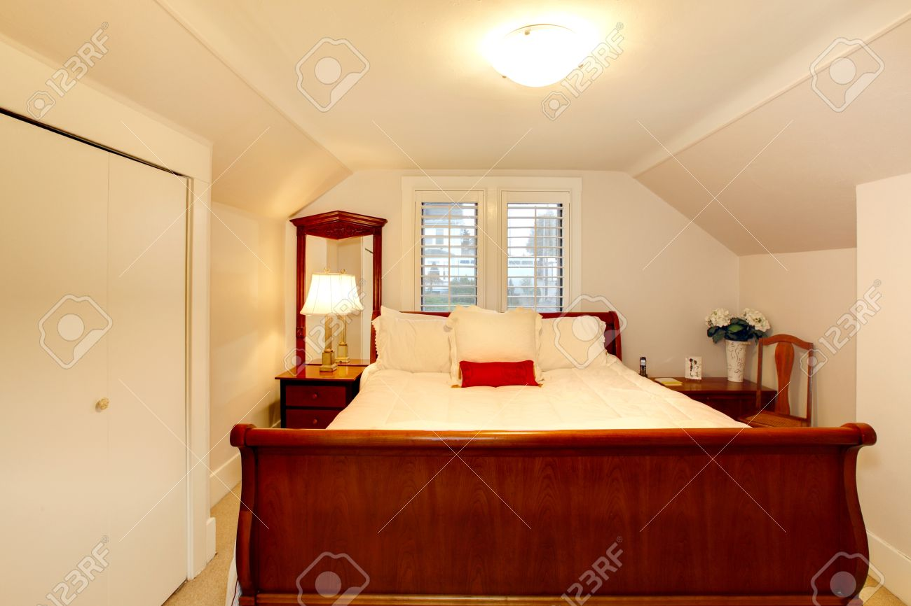 Attic bedroom with low ceiling and large bed.
