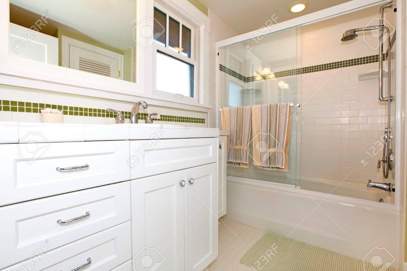Salle de bains avec baignoire et vert armoires blanches banque d ...
