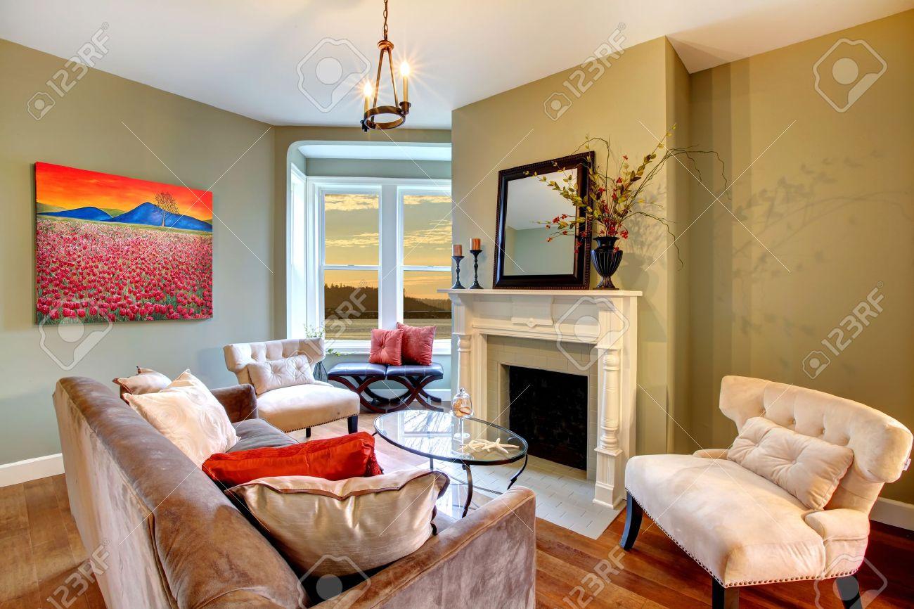 Salon avec murs verts et canapé marron.