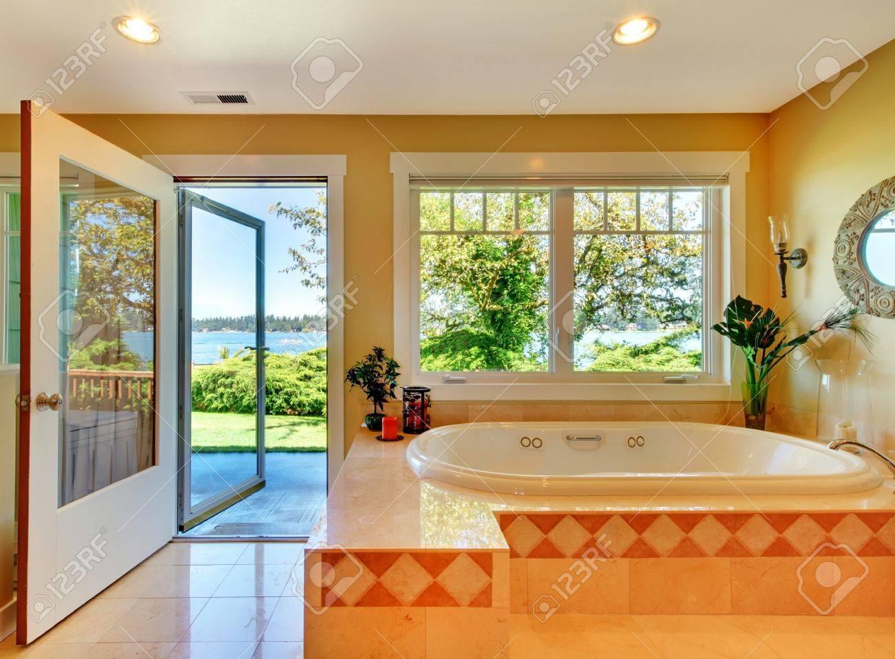 Gran cuarto de baño con bañera Ver amarillo y el lago y la puerta abierta.