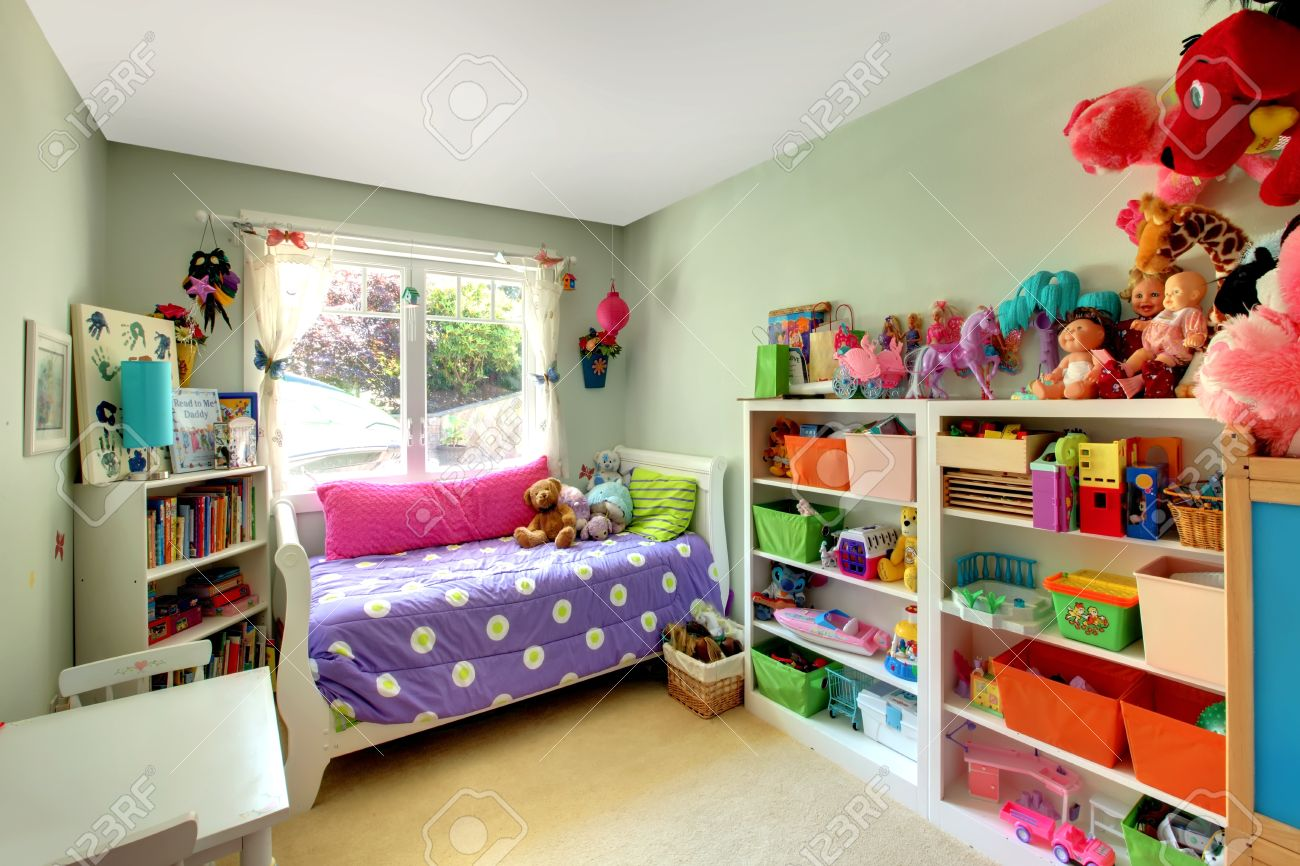 Kids Bedroom Green kids bedroom with green walls and purple bed and may toys. stock