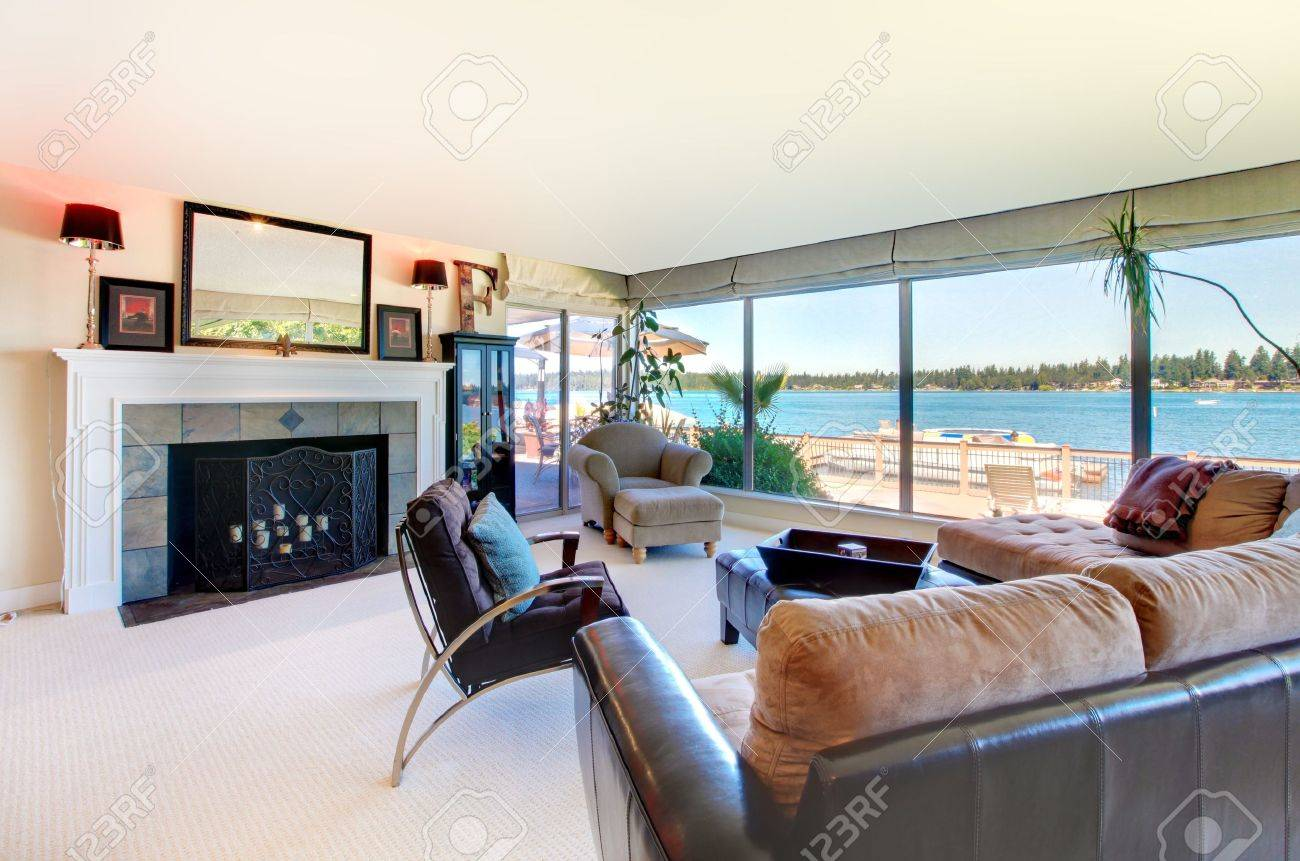 Living room with fireplace, modern furniture and water view with large windows. Stock Photo - 12621251