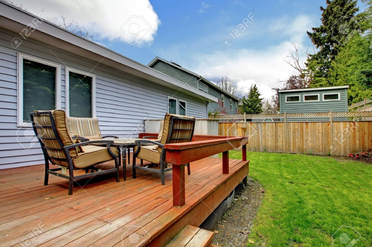 Simlle Small Grey House Deck With Outdoor Furniture And Fenced Back Yard.  Stock Photo