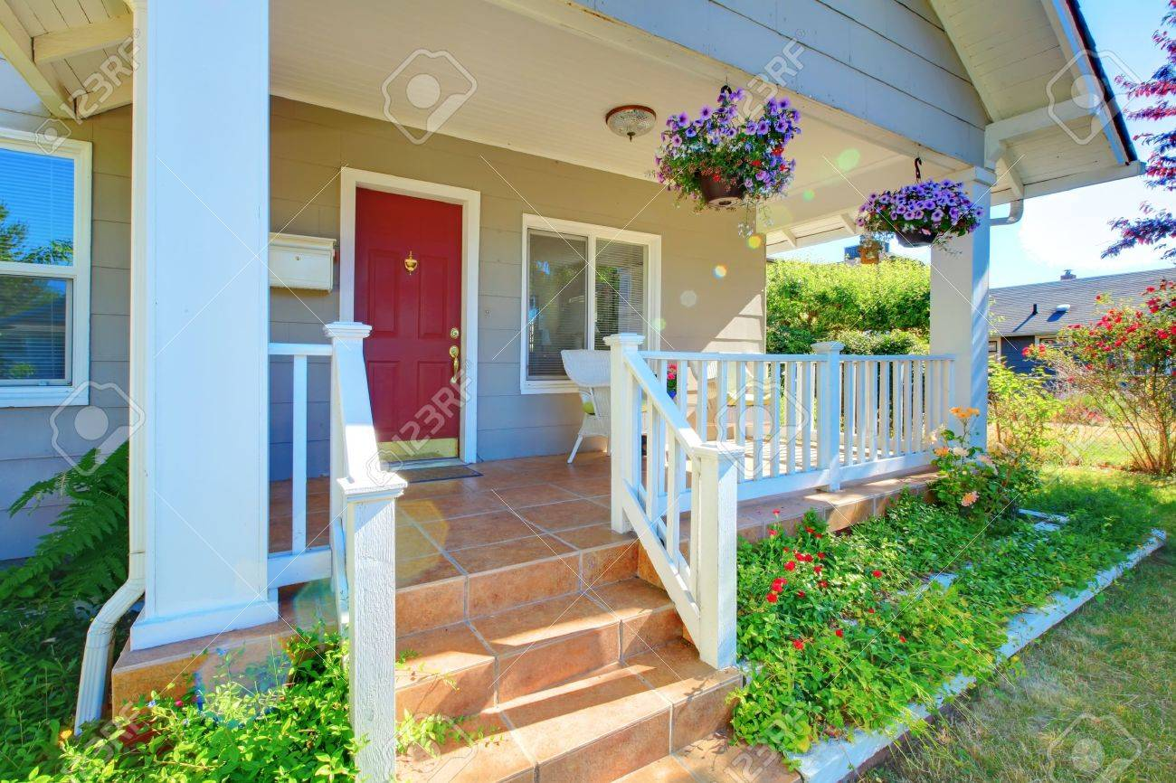 red door grey house. Grey House Porch With Red Door, White Railings And Purple Flowers. Stock Photo - Door T