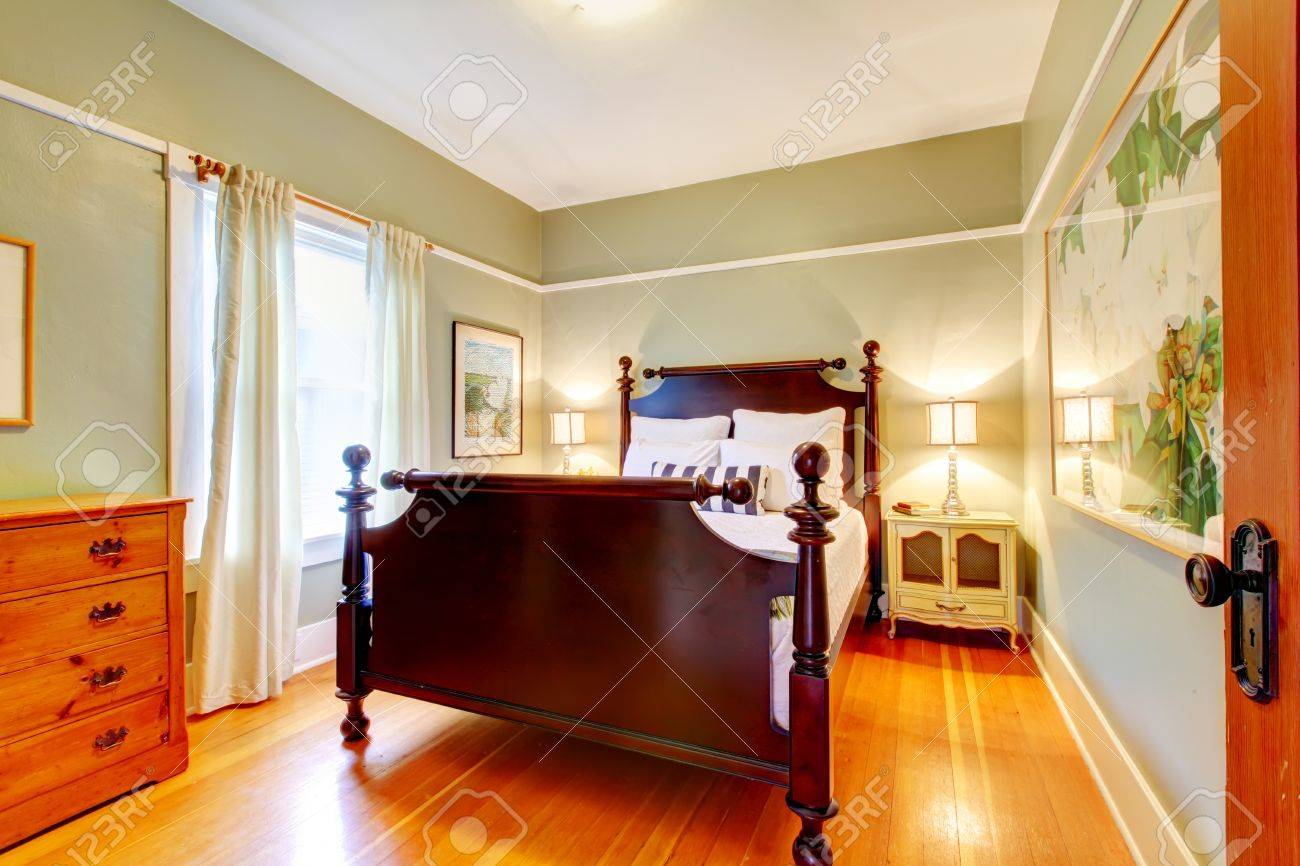 Green bedroom with cherry hardwood and dark bed. Stock Photo - 12760832