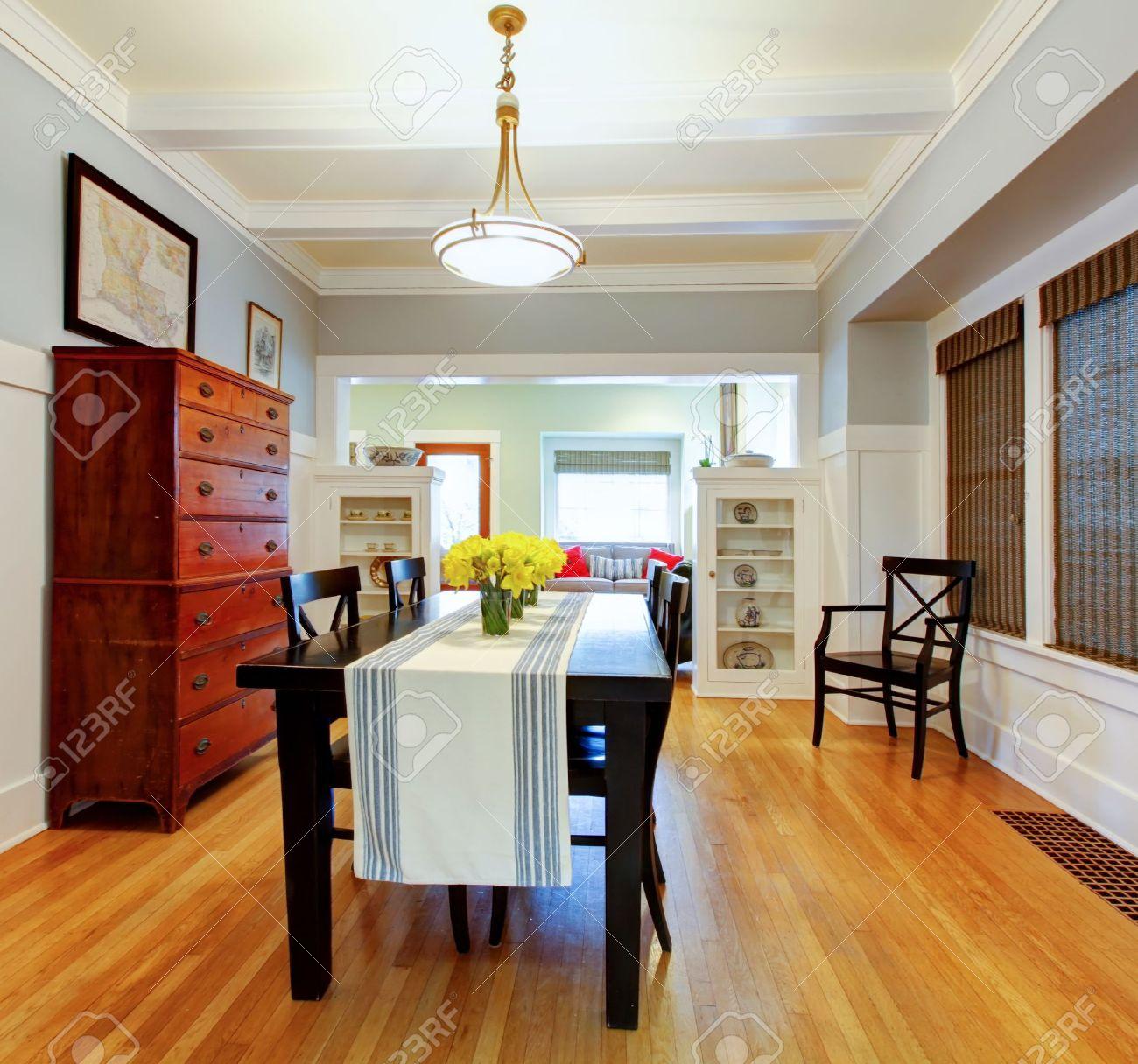 Comedor interior de la habitación con una mesa grande de color negro y una  cómoda de madera con paredes grises azules.